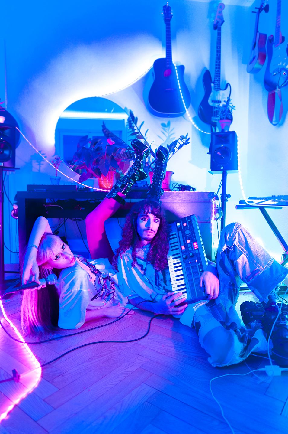 Portrait of TBC duo in their music homestudio in blue light